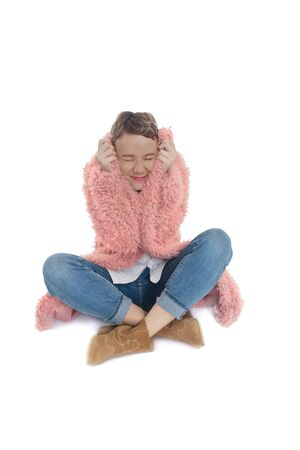 Girl in a pink faux fur coat is freezes. Short haired woman coves her ears on white background.