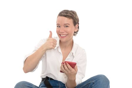 Girl with red phone in white shirt and blue jeans showing thumb up. Smiling woman isolated on white background. Stok Fotoğraf
