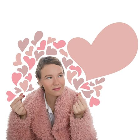 Blonde girl with short hair is smiling and showing heart sign hands. Woman in pink fur coat isolated on white background. Zdjęcie Seryjne
