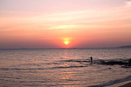 Fisherman on sea pink sunset background. Beautiful color clouds. Reklamní fotografie