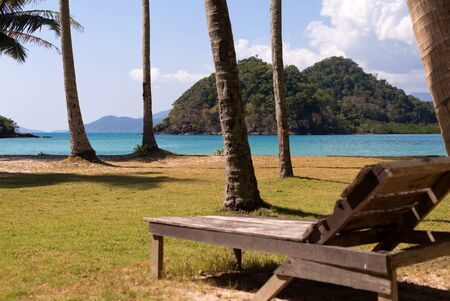 Wooden beach chair on tropic palm tree island. Blur background