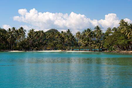 Tropical island sand beach on the sea. Blue sky with clouds.