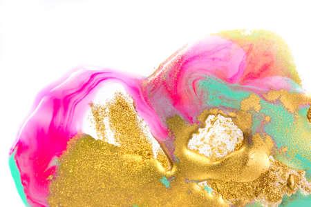 Gold, green and pink inks splattered on white paper background. Golden glitter 免版税图像