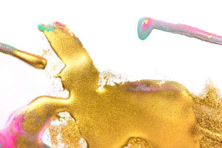 Gold and pink inks splattered on white paper background. Golden glitter