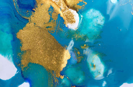 Gold and blue mixed inks splattered on white paper background.