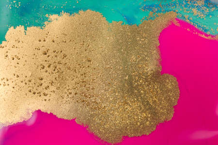 Piles of gold sequins on blue and pink smudges of paint. Abstract pattern.