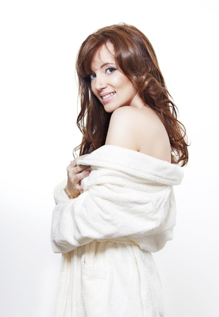 beautiful smiling girl with perfect skin and long dark hair in a bathrobe on white background photo