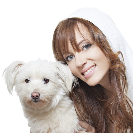 beautiful smiling girl with perfect skin with a fluffy white dog on a white background