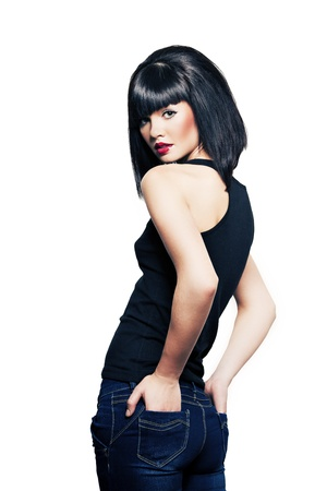 beautiful girl with perfect skin in a black shirt and jeans with black short hair and bright red lipstick Stock Photo