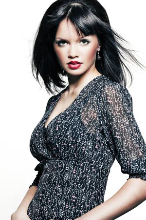 beautiful girl with perfect skin in a dark dress with black short hair and bright red lipstick photo