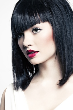 beautiful girl with perfect skin and bright red lipstick, black straight hair on a white background photo