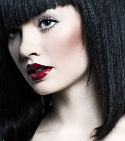 beautiful girl with perfect skin and bright red lipstick, black straight hair on a white background