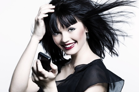 beautiful laughing girl with perfect skin and bright red lipstick, black straight hair in the wind, developing, and with the phone in his hand on a white background