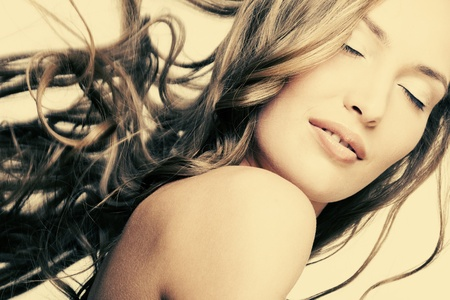 belle fille avec une peau parfaite et � long svetlysm cheveux flottants sur un fond jaune, s�pia photo