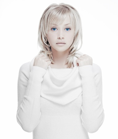 beautiful girl with perfect skin, blond hair and blue eyes on a light background in white sweater