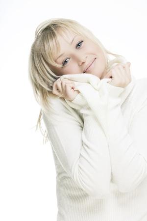 sueter: hermosa chica con la piel perfecta, el pelo rubio y ojos azules sobre un fondo claro con un suéter blanco
