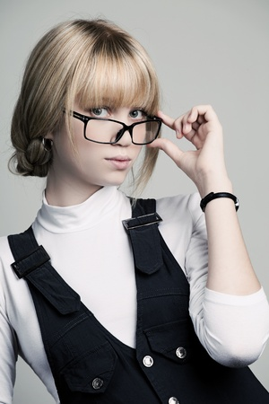 Beautiful young woman posing in business suit and glasses. Isolated over white background. photo