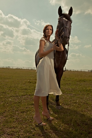 beaubeautiful girl in a white gown with horse on nature