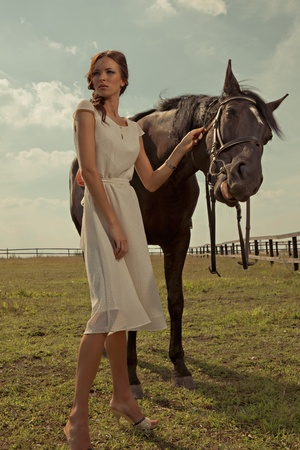 beautiful girl in a white gown with horse on nature photo