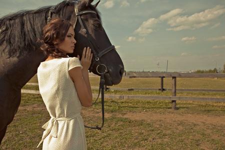 black horse: hermosa chica en un vestido blanco con el caballo en la naturaleza