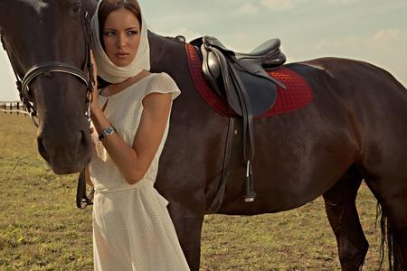 femme et cheval: belle fille dans une robe blanche à cheval sur la nature Banque d'images