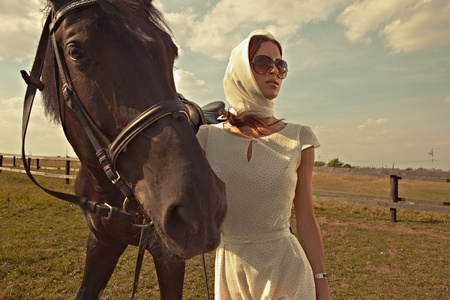 outdoor glamour: beautiful girl in a white gown with horse on nature