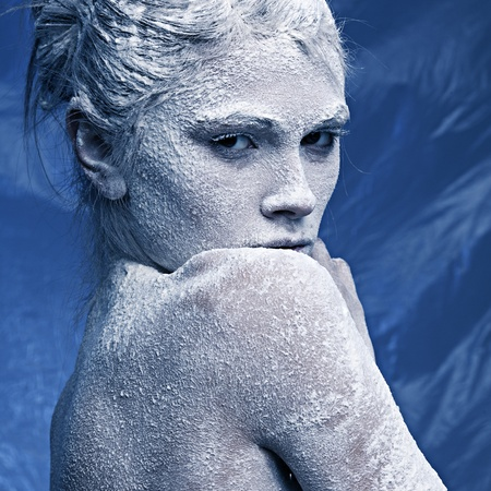 Portrait of a beautiful girl in the frost on his face on a blue ice background Stock Photo