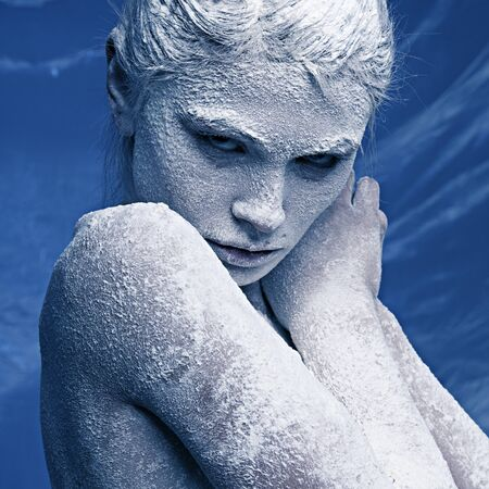 Portrait of a beautiful girl in the frost on his face on a blue ice background photo