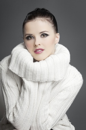 woman sweater: beautiful girl with dark hair in a white sweater with a gray background Stock Photo