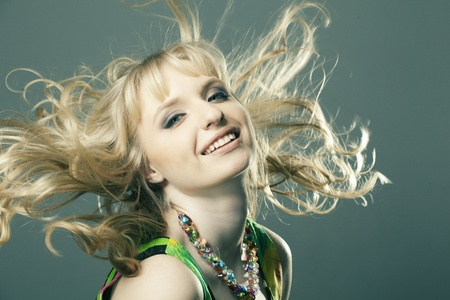 portrait of a beautiful girl with perfect skin, blond curly hair and developing jewelry photo