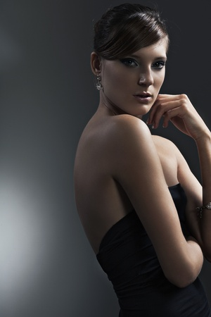 beautiful girl with perfect skin in black dress with jewelry on a dark background