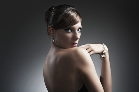 beautiful girl with perfect skin in black dress with jewelry on a dark background photo