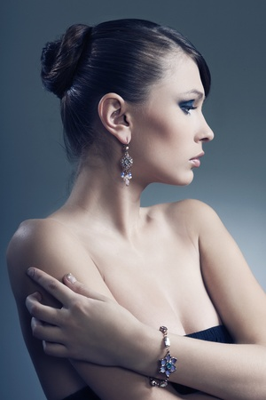 beautiful woman with perfect skin in black dress with jewelry