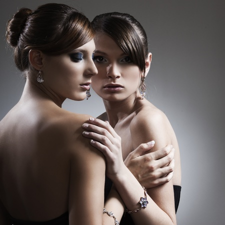 two beautiful woman with perfect skin in black dress with jewelry
