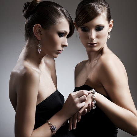 two beautiful woman with perfect skin in black dress with jewelry photo