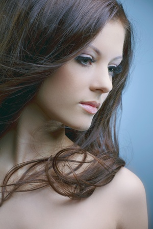 beautiful woman with perfect skin and long dark luxuriant hair on a dark background