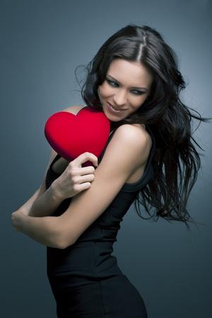 saint valentin coeur: Valentin Belle femme souriante avec un cadeau en forme de coeur dans ses mains