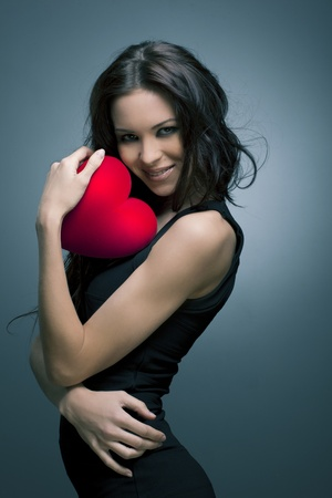 Valentine s Day  Beautiful smiling woman with a gift in the form of heart in his hands
