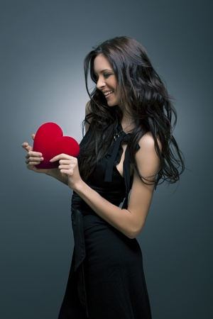 Valentine s Day  Beautiful smiling woman with a gift in the form of heart in his hands Stock Photo - 12782836