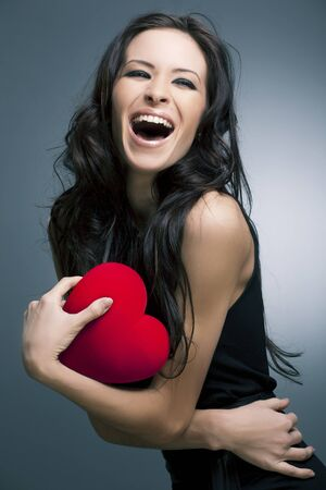Valentine s Day  Beautiful smiling woman with a gift in the form of heart in his hands Stock Photo - 12782837