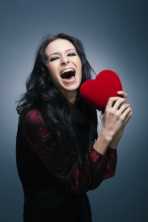 Valentine s Day  Beautiful smiling woman with a gift in the form of heart in his hands Stock Photo - 12782839