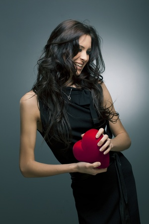 Valentine s Day  Beautiful smiling woman with a gift in the form of heart in his hands photo