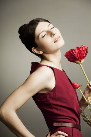 portrait of a beautiful woman with perfect skin and hair in a red dress with a flower on dark background Stock Photo - 12844523