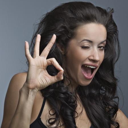 gente loca: Una mujer hermosa que est� mostrando un signo bien de las emociones positivas Foto de archivo