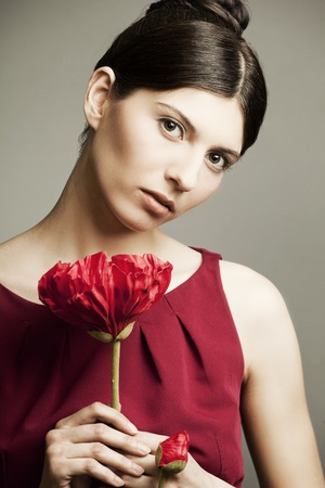 portrait of a beautiful woman with perfect skin and hair in a red dress with a flower on dark background photo