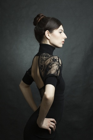 portrait of a beautiful woman with perfect skin and hair in a black dress on dark background photo