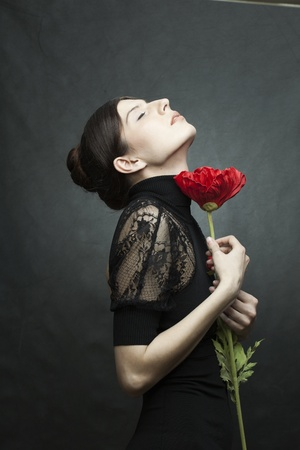 portrait of a beautiful woman with perfect skin and hair in a black dress with a flower on dark background photo