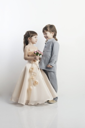 Portrait of two beautiful little boys and girls in wedding dresses from the bridal bouquet on white background