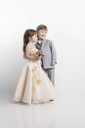 Portrait of two beautiful little boys and girls in wedding dresses from the bridal bouquet on white background photo