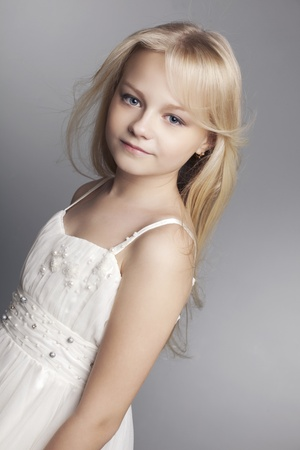 beautiful little girl with long hair svetlyi on a dark background photo